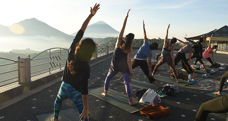 Sunrise yoga facing Mount Batur, one of the highlights of your yoga retreat at Oneworld Retreats in Ubud, Bali.